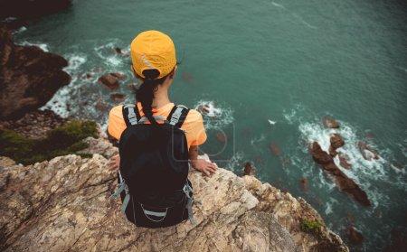 Foto de Mujer caminante sin miedo sentarse en el borde del acantilado junto al mar - Imagen libre de derechos