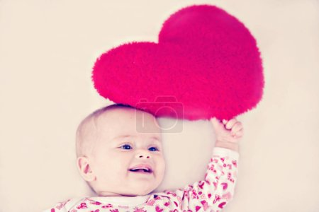 Photo for Cute toddler girl with heart pillow - Royalty Free Image