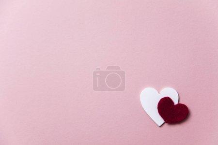 weiße Herzen auf pastellrosa Hintergrund.