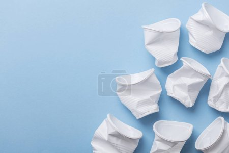 Photo pour Tasses en plastique blanc à usage unique sur fond bleu - image libre de droit