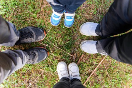 Photo for Family standing in sportive shoes on green grass - Royalty Free Image