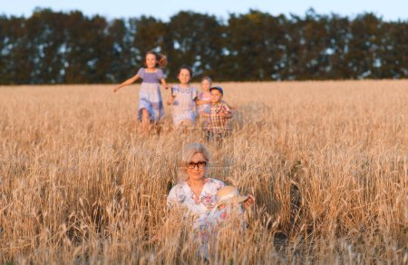 Photo for Happy children running to grandmother sitting in wheat - Royalty Free Image