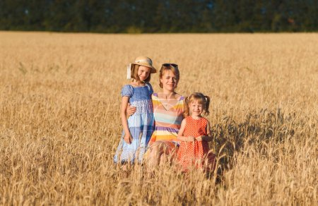 Photo for Mother hugging two daughters in wheat field at sunny day - Royalty Free Image