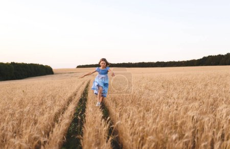 Photo for Girl in blue dress running in wheat field - Royalty Free Image