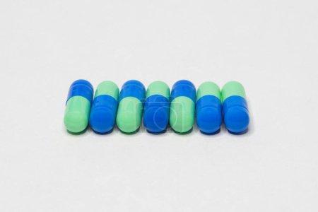 Photo pour Pilules médicinales. Comprimés. Médicament pharmaceutique, Gros plan sur la pile de comprimés bleus et verts - capsule. Pilules et comprimés sur fond blanc - image libre de droit