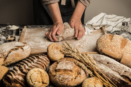 Photo for Baker's hands kneading raw dough on pastry board. Making whole grain loaf of bread - small bakery scenery. - Royalty Free Image