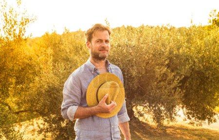 Photo pour Fermier ou jardinier caucasien retenant un chapeau de paille tout en restant devant une oliveraie. Agriculture ou jardinage - paysage extérieur de pays, lumière de coucher du soleil d'or. - image libre de droit