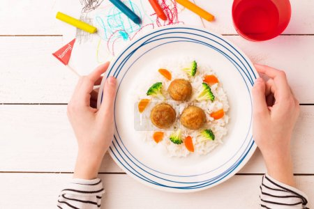 Photo pour Repas d'enfant - boulettes de viande, riz, brocoli et carotte. Dîner coloré - assiette dans les mains de l'enfant sur une table en bois blanc. Plaque capturée d'en haut (vue de dessus, position plate ). - image libre de droit