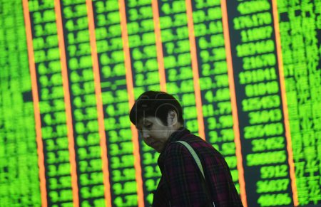 A concerned Chinese investor walks past a screen d...