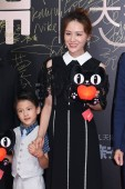 Chinese singer and actress Ye Yiqian, right, and her son pose as they arrive on the red carpet for Tmall baby awards in Shanghai, China, 17 May 2018.