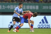 Matias Vecino, left, of Uruguay national football team challenges a player of Czech Republic national football team in their semi-final match during the 2018 Gree China Cup International Football Championship in Nanning city, south China's Guangxi Zh
