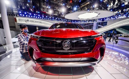 Photo for A Chinese worker cleans a Buick Enspire electric concept SUV of General Motors (GM) on display during a preview of the 15th Beijing International Automotive Exhibition, also known as Auto China 2018, in Beijing, China, 24 April 2018 - Royalty Free Image