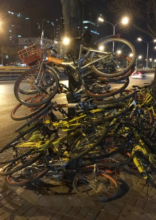 Photo for Bicycles of Chinese bike-sharing services Mobike and ofo are piled up and leant on trees by local residents on a street in Beijing, China, 6 December 2017 - Royalty Free Image