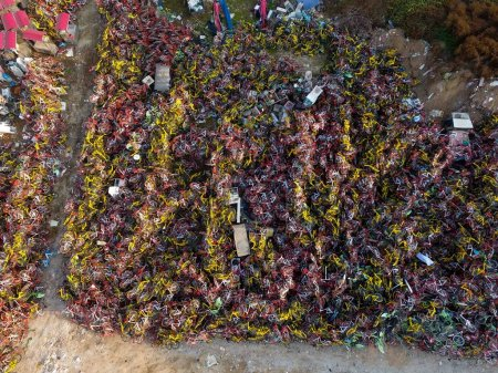 Photo for Abandoned bicycles of Mobike (orange), ofo (yellow) and other Chinese bike-sharing services are piled up at an open space in Zhengzhou city, central China's Henan province, 14 November 2017. - Royalty Free Image