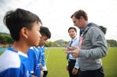 Former Dutch football player Ronald de Boer, right, interacts with young football players during the cooperation signing ceremony of R&F football club and AFC Ajax in Meizhou city, south China's Guangdong province, 27 November 2017