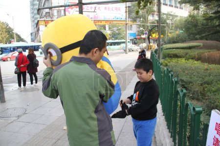 Foto de Nine-year-old Chinese boy Xin Xin, who plays Minion to raise money for the treatment of his 7-year-old younger brother Xiao Jie with leukemia, prepares to wear the costume near a park in Ji'nan city, east China's Shandong province, 31 October 2017 - Imagen libre de derechos