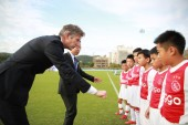 Former Dutch football play Edwin van der Sar, left, CEO of Amsterdamsche Football Club Ajax (AFC Ajax), interacts with young football players during the cooperation signing ceremony of R&F football club and AFC Ajax in Meizhou city, south China's Gua