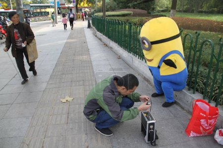 Foto de Nine-year-old Chinese boy Xin Xin, who plays Minion to raise money for the treatment of his 7-year-old younger brother Xiao Jie with leukemia, sings to the music near a park in Ji'nan city, east China's Shandong province, 31 October 2017 - Imagen libre de derechos