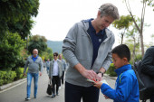 Former Dutch football play Edwin van der Sar, left, CEO of Amsterdamsche Football Club Ajax (AFC Ajax), signs autographs for a young football player during the cooperation signing ceremony of R&F football club and AFC Ajax in Meizhou city, south Chin