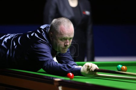 Photo for John Higgins of Scotland plays a shot to Martin Gould of England in their quarterfinal match during the 2017 Shanghai Masters snooker tournament in Shanghai, China, 16 November 2017 - Royalty Free Image