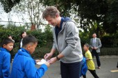 Former Dutch football play Edwin van der Sar, right, CEO of Amsterdamsche Football Club Ajax (AFC Ajax), signs autographs for a young football player during the cooperation signing ceremony of R&F football club and AFC Ajax in Meizhou city, south Chi