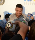 Brazilian football star Ronaldo Luis Nazario de Lima, center, commonly known as Ronaldo, signs autographs as he visits one of his soccer schools in Shanghai, China, 28 May 2017.