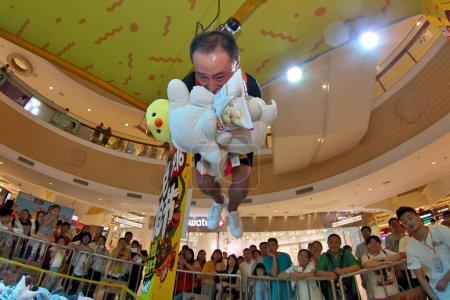 Foto de Un participante que se abusa y lleva guantes de boxeo para actuar como una máquina de garra humana intenta agarrar juguetes en un centro comercial en la ciudad de Yantai, la provincia de Shandong, al este de China, el 16 de septiembre de 2017 - Imagen libre de derechos