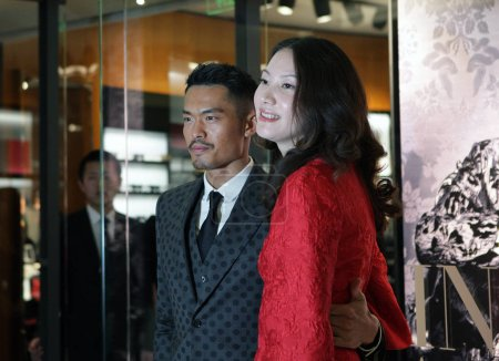Photo for --FILE--Chinese badminton superstar Lin Dan, left, and his wife Xie Xingfang attends a promotional event for Dolce & Gabbana in Beijing, China, 20 March 2015 - Royalty Free Image