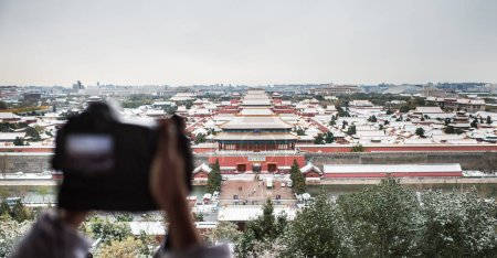 Photo for A tourist takes photos of the Palace Museum, also known as the Forbidden City, in the snow in Beijing, China, 21 November 2016 - Royalty Free Image