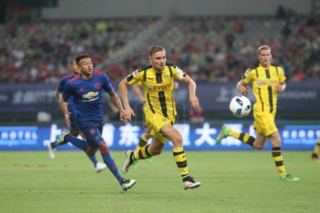 Photo for Marcel Schmelzer of Borussia Dortmund, right, competes against players of Manchester United during the Shanghai match of the 2016 International Champions Cup at the Shanghai Stadium in Shanghai, China, 22 July 2016. - Royalty Free Image