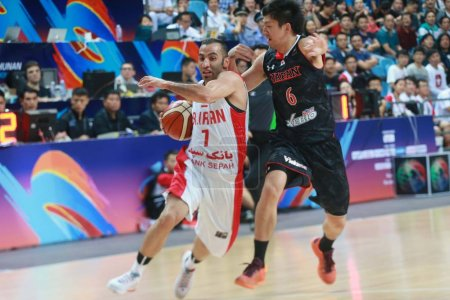 Photo for Makoto Hiejima of Japan, right, challenges Mahdi Kamrani of Iran in a group match during the 2015 FIBA Asia Champions for Men in Changsha city, central China's Hubei province, 23 September 2015. - Royalty Free Image