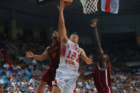 Photo for Li Gen of China, center, drives to the basket to score against Qatar in their second round match during the 2015 FIBA Asia Championship in Changsha city, central China's Hunan province, 29 Septemebr 2015 - Royalty Free Image