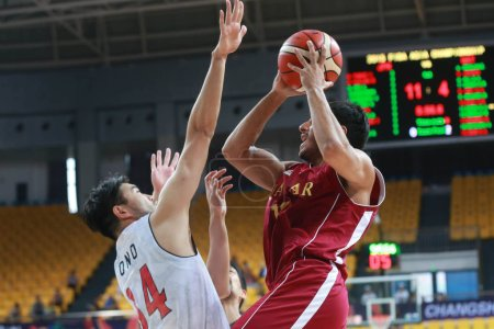 Photo for Ryumo Ono of Japan, left, challenges a player of Qatar in a quarter-final match during the 2015 FIBA Asia Champions for Men in Changsha city, central China's Hubei province, 1 October 2015 - Royalty Free Image