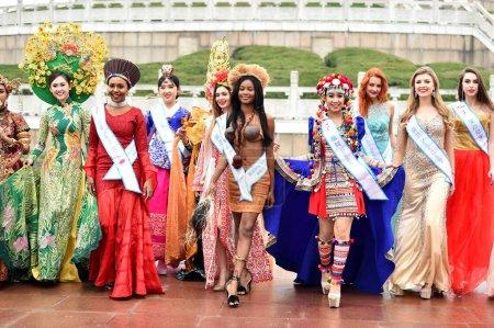 Photo pour Les participants vêtus de costumes traditionnels ou robes de soirée prendre part à une séance photo en plein air pour la 53e concours Miss tous les pays, dans la ville de Nanjing, province de Jiangsu du Nord-est de la Chine, 28 janvier 2019 - image libre de droit