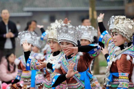 """Chinese people of Miao ethnic group dressed in traditional costumes and headwears dance and play the """"Lusheng,"""" a reed-pipe wind instrument, at the traditional social party """"Datongnian"""" in Rongshui Miao Autonomous county, Liuzhou city, south China's"""