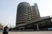 -A cyclist rides past the headquarters building of Fosun Group in Shanghai, China, 20 February 2014