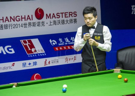 Photo for Ding Junhui of China chalks his cue as he considers a shot against Martin Gould of England during their second round match of the 2014 World Snooker Shanghai Masters in Shanghai, China, 11 September 2014 - Royalty Free Image