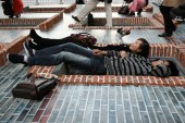 Visitors lie on a model of Shikumen building on the ground, looking at or taking photos of themselves reflected by a huge mirror erected at a 45-degree angle, during an exhibition by Argentinian artist Leandro Erlich at the JingAn Kerry Center, Shang
