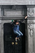 A visitor poses on a model of Shikumen building, which is reflected by a huge mirror erected at a 45-degree angle, creating the illusion that she is performing a gravity-defying stunt during an exhibition by Argentinian artist Leandro Erlich at the J