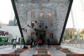 Visitors pose on a model of Shikumen building on the ground, looking at themselves reflected by a huge mirror erected at a 45-degree angle, during an exhibition by Argentinian artist Leandro Erlich at the JingAn Kerry Center, Shanghai, China, 18 Nove