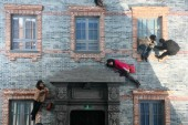 Visitors pose on a model of Shikumen building, which is reflected by a huge mirror erected at a 45-degree angle, creating the illusion that they are performing gravity-defying stunts during an exhibition by Argentinian artist Leandro Erlich at the Ji