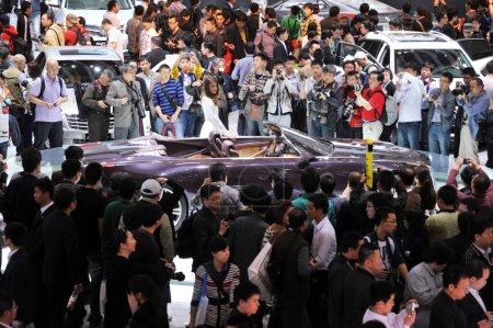 Visitors crowd around a Cadillac