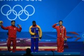 Gold medalist Kim Un Guk of North Korea, right, salutes next to silver medalist Oscar Albeiro Figueroa Mosquera of Colombia, center, and bronze medalist Irawan Eko Yuli of Indonesia at the award ceremony of the mens 62kg weightlifting event during th