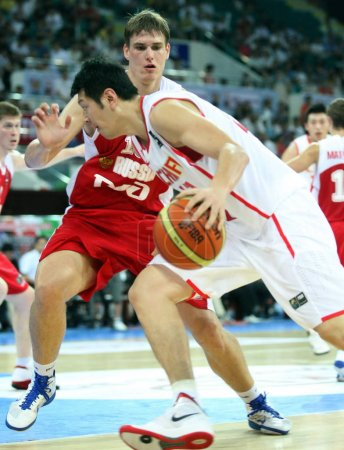 Photo for Chinas Mo Ke tries to breakthrough against Russia during their FIBA Stankovic Continental Cup basketball match in Guangzhou, south Chinas Guangdong province, 8 August 2011 - Royalty Free Image