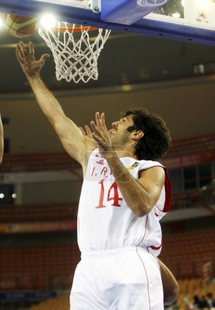 Photo for Irans Samad Bahrami tries to shoot during the second round match against Lebanon at the 26th FIBA Asia Championship in Wuhan city, central Chinas Hubei province, 20 September 2011 - Royalty Free Image
