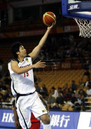 Photo for Joji Takeuchi of Japan plays a shot against the United Arab Emirates (UAE) in their second round match during the 26th FIBA Asia Championship in Wuhan city, central Chinas Hubei province, 19 September 2011 - Royalty Free Image