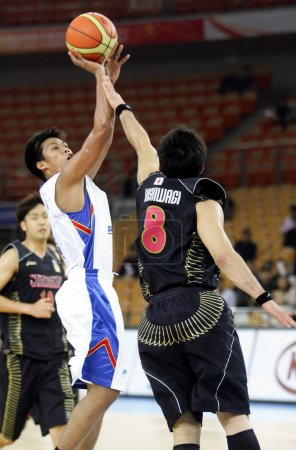 Photo for Shinsuke Kashiwagi of Japan, right, tries to block a shot by Mark Andy Barocca of the Philippines in their second round match during the 26th FIBA Asia Championship in Wuhan city, central Chinas Hubei province, 20 September 2011 - Royalty Free Image