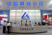 Employees are seen at the stand of Aluminum Corporation of China, known as CHINALCO, parent company of Aluminum Corporation of China Limited, known as CHALCO, during an exhibition in Shanghai, China, July 1, 2009.