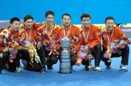 Photo for (From L) Chinas team members, Chen Qi, Ma Long, Wang Liqin, head coach Liu Guoliang, Wang Hao and Ma Lin pose with the trophy in front of the podium of the World Team Table Tennis Championships after winning the mens final match against South Korea i - Royalty Free Image