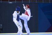 Li Zhi of China (L) lands a kick on Erick Osoronio of Mexico in the mens 68kg catagory in the Good Luck Beijing 2008 International Taekwondo Invitational Tournament at the University of Science and Technology Gymnasium in Beijing, February 27, 2008.